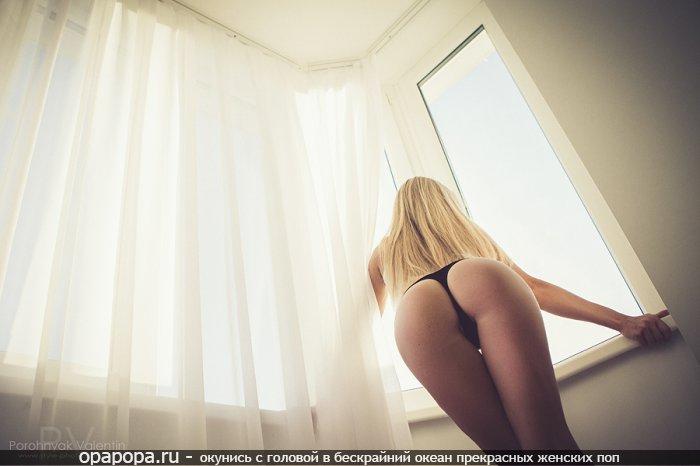 Блондиночка Нина со спортивной смачной попкой у окна в трусиках-тангах