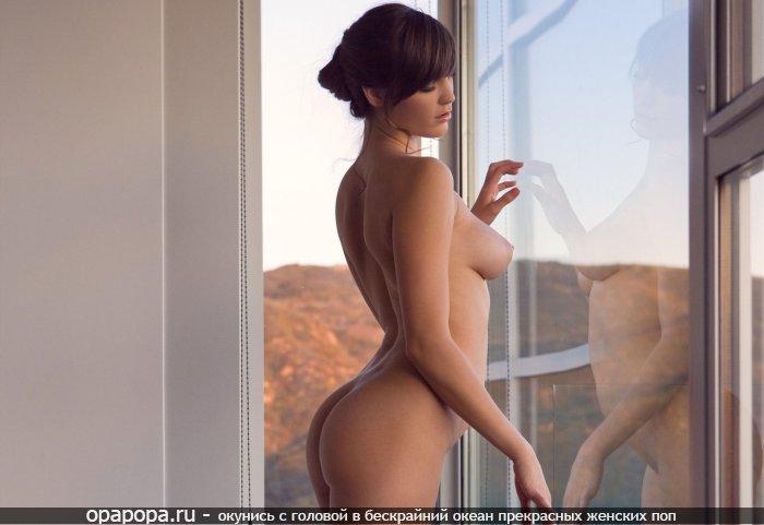 Брюнеточка Христина с небольшой задницей у окна без трусиков с сочной грудью