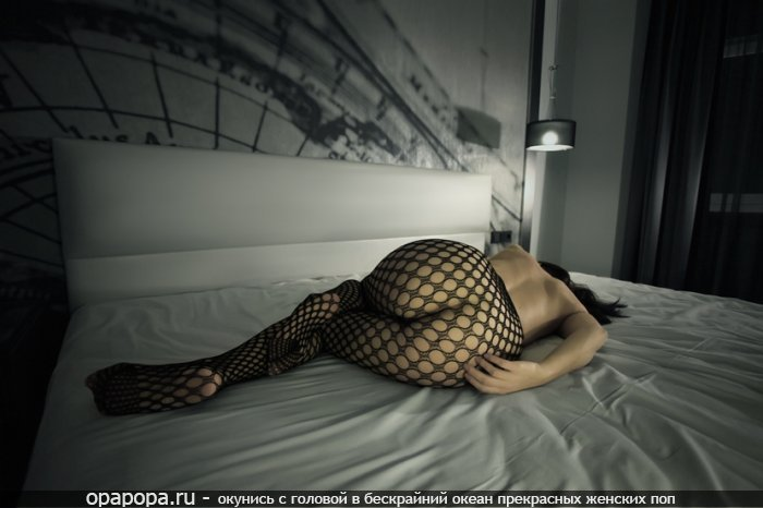 Девушка с эффектной попой на кровати в колготках