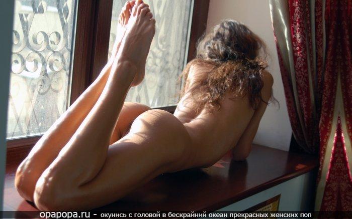 Девушка с привлекательной смачной попой у окна