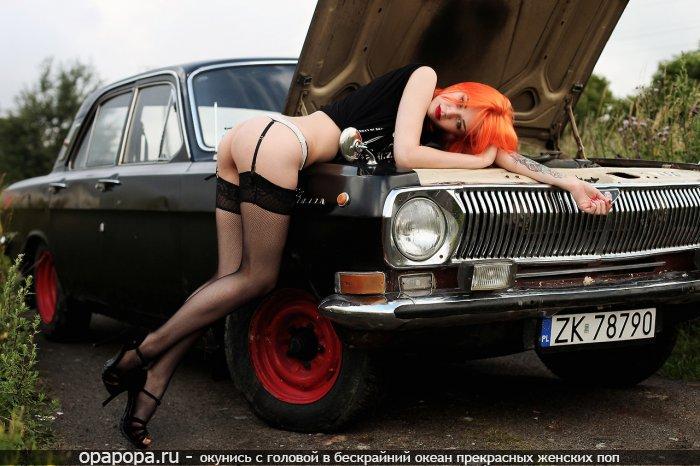 Фото: рыжей с девичьей небольшой попкой у машины на улице в стрингах и чулках