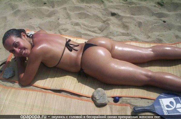 Фото: смуглой девушки с лакомой попкой на пляже в мини купальнике в масле
