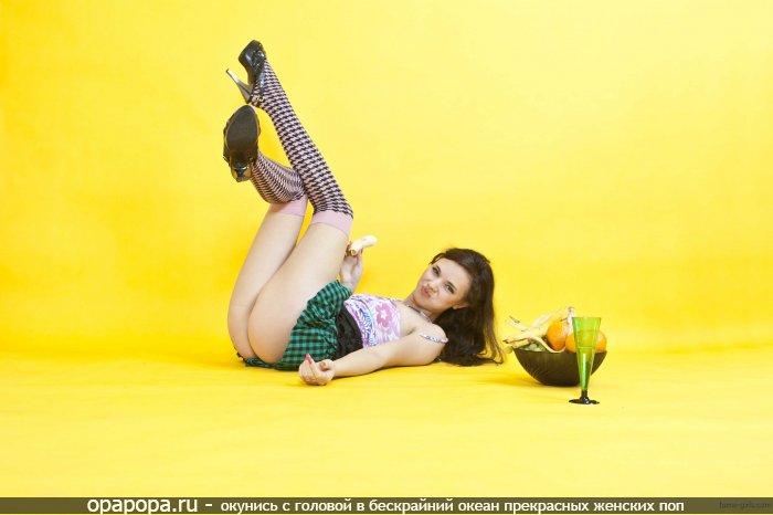Маленькая старлетка сосет банан на полу с привлекательной попой под юбкой