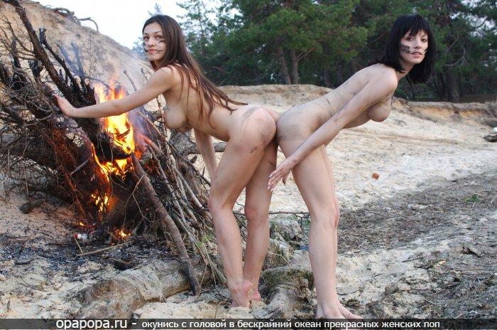 Подружки с большими сиськами развели костер и греют свои лакомые и небольшие попки на улице без трусиков