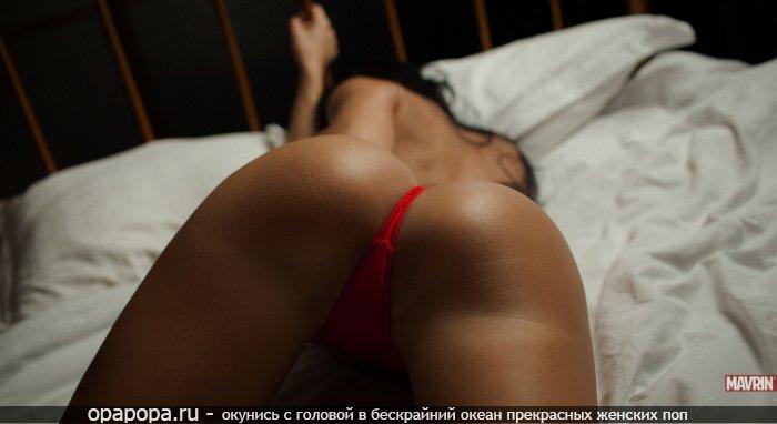 Смуглая девушка на кровати в мини-трусиках